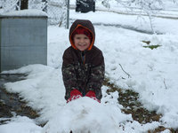 Image: Landon has a big smile — Four year old, Landon Torres, helps the Nash family with their large snowman.  He is in charge of the head.