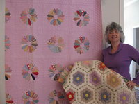 "Image: Suzzy and a cherished gift — ""I love old hand quilted quilts. The quilt I am holding, a Grandmother's Flower Garden quilt, was given to me by my uncle after my Aunt Barbara died after a long illness from a Lynch Syndrome related cancer arrising in the urinary track."""