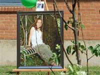 Image: A portrait of Samantha Nance on display next to her tree — A portrait of Samantha (Shelley) Nance stands next to the tree dedicated in Shelley's memory that was planted in the courtyard at Italy High School to commemorate her amazing life that ended much to soon in the fall of 2009.