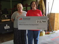 Image: Milford Fire Department grant. — Carolyn Parker and Peggy Duke of Fireman's Fund Insurance presenting the bunker gear grant.
