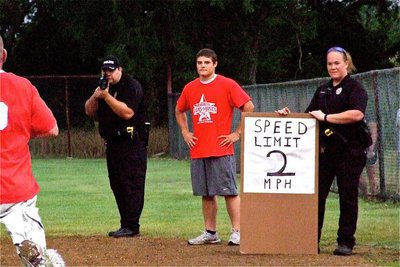 Image: I.F.D.'s Ethan Simon seems concerned with the speed trap put in place along the first base line by I.P.D. officers Eric Tolliver and Jamie Thompson.