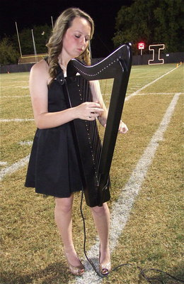 Image: Maddie Pittman plays the harp as the Homecoming Court is introduced along with their escorts.