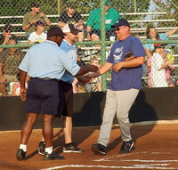Image: Italy Police Chief Diron Hill greets umpires Robert Hodge and Lee Joffre during the pre-game introductions.