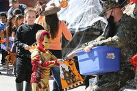 Image: Iron Man collects candy from a parent dressed as a Duck Dynasty character.