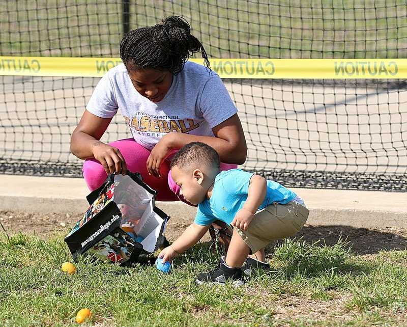 Image: Jaiden Saxon with his mom Jameka plays a little football with an egg.