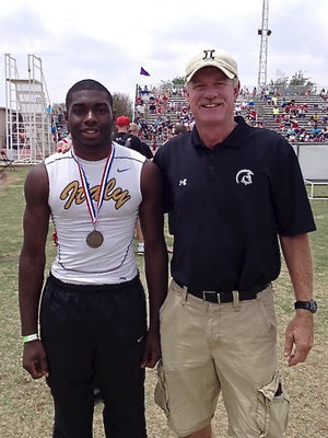 Image: Senior Gladiator TaMarcus Sheppard displays his silver medal in the high jump with Italy's AD/HFC Charles Tindol at Tindol's old stomping grounds in Abilene.