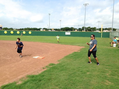 Image: Softball Coach Tina Richards encourages her hitters as they make their way down the first base line.