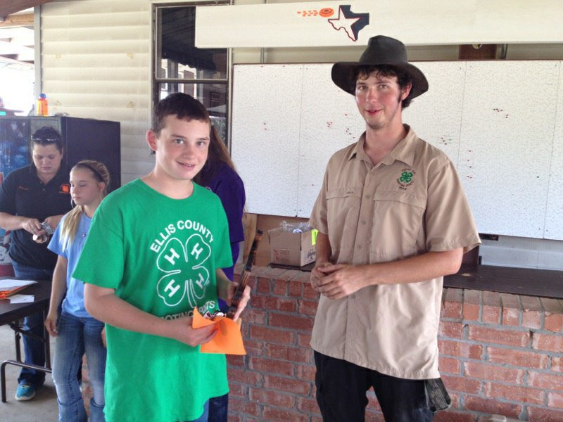 Image: Hunter Hinz, left, accepts his trophy at the Ellis County tournament. Right, is Matt Dawson, 2014 Maypearl High School graduate and graduate of the Ellis County Shooting Sports 4-H Club. Dawson won the adult division and remains with the club as a coach.