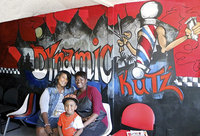 "Image: Dynamic Kut'z owner Cynthia Singleton Chance, her nephew Adrian ""Deuce"" Griffin and Beautician Na'Koia Hailey, aka KoKoFiveO, pose in front of the wall mural painted by Cynthia herself. It was Customer Appreciation Day at Dynamic Kut'z with music, food and haircuts for all."