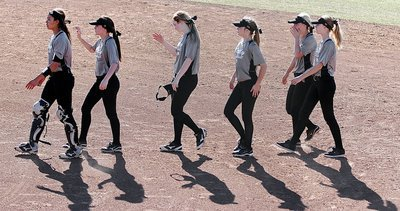 Image: The shadows of April Lusk(7), Cassidy Childers(3), Kelsey Nelson(14), Kirsten Viator(22), Bailey Eubank(1) and Paige Cunningham(21) walk out to shake hands with Palmer's squad after the contest.