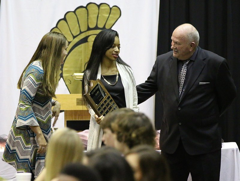 Image: Coaches Holly Bradley and Johnny Jones present T'Keya Pace with the Cross-Country MVP Award with her name engraved on the plaque.