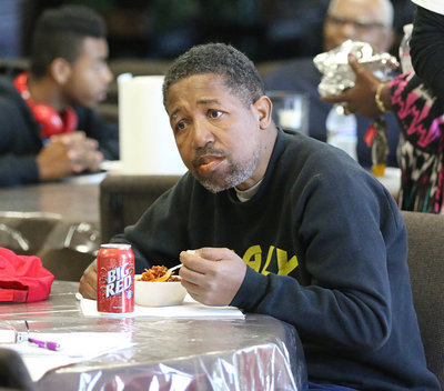Image: Dean Reese enjoys his first bowl of chili while studying his next pot of chili to taste.
