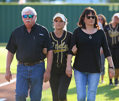Image: Italy Lady Gladiator senior Cassidy Childers is being escorted by her parents before the game while being honored during Senior Day at Johnny Jones Field.