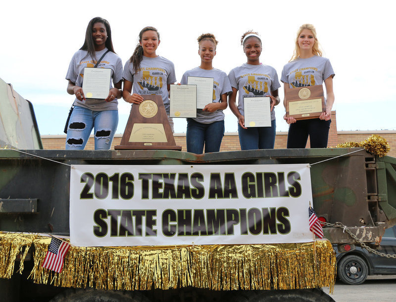 Image: The Italy Lady Gladiator 2016 Conference AA State Champion Track Team members Janae Robertson, April Lusk, T'Keyah Pace, Chardanae Talton and Halee Turner present their City of Italy proclamations and state trophies. The team  rode in the back of a camo painted city dump truck during a downtown parade held in their honor on Friday.