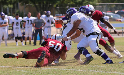 Image: Austin College junior nose guard Zain Byers (#50 in Crimson) latches on to a Whittier Poet running back.