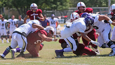 Image: Austin College junior nose guard Zain Byers (#50 in Crimson) hangs on by the jersey until help arrives to bring down a Whittier Poet running back.