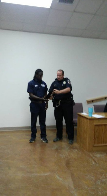 Image: Police Chief Cameron Beckham presents Greg Anderson a plaque honoring him for bravery.