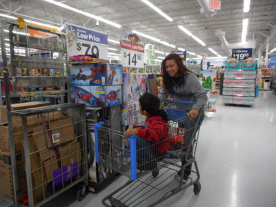 Image: April Lusk helps one of the students with his shopping.