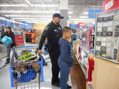 Image: Officer Baron gladly helps a student shop for his family.