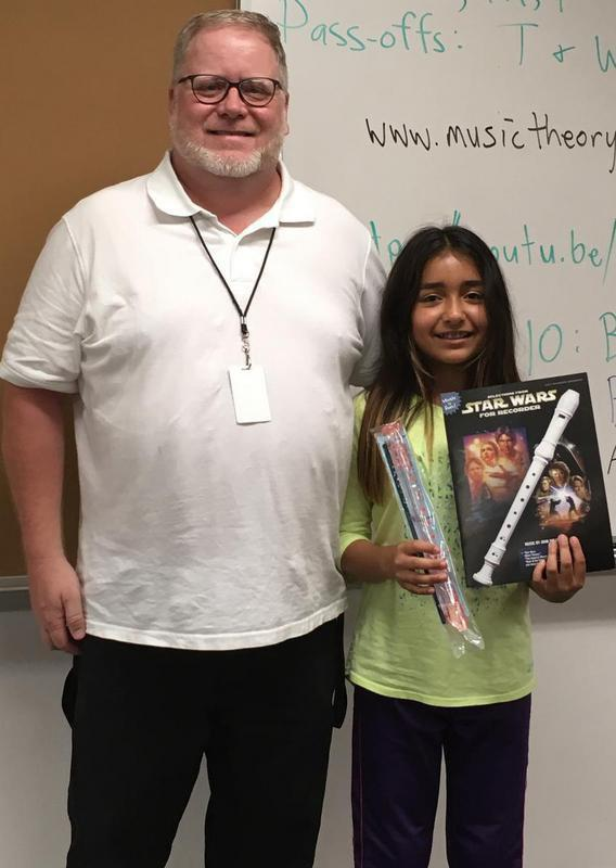 "Image: Mr Graves, 5th grade music teacher; Itzy; and her prize winnings, including a new recorder and a book of ""Star Wars"" tunes for the recorder."